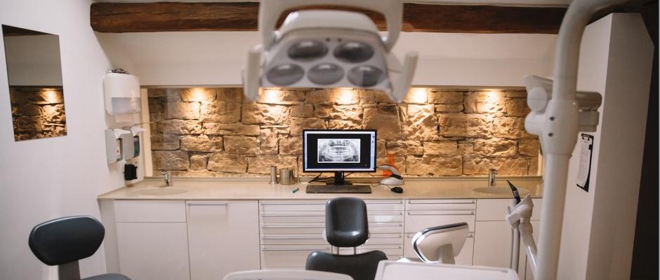 Zahnarztstuhl vor beleuchteter Bundsandsteinwand